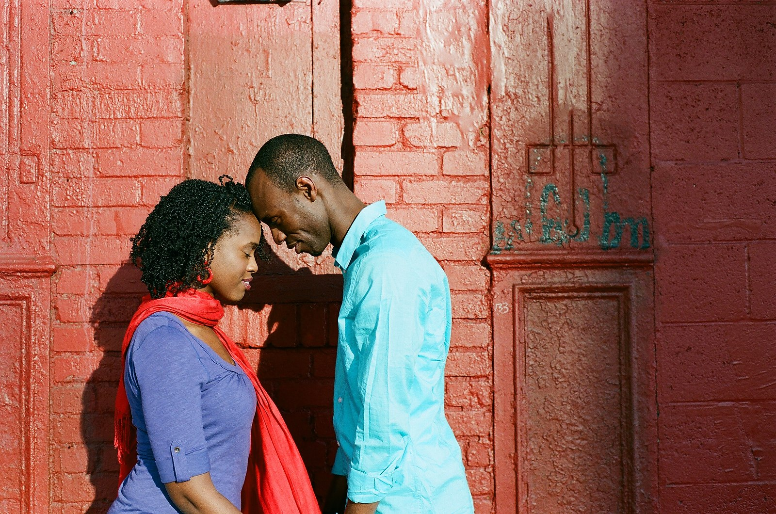 engaged couple with foreheads touching red background