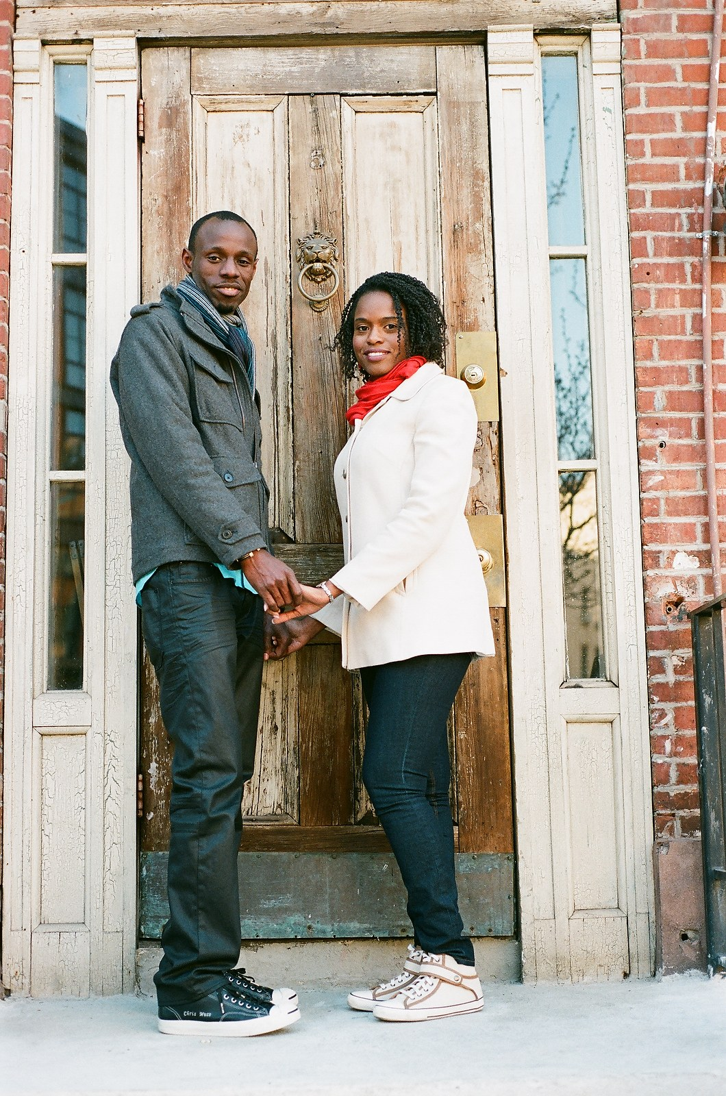 engaged couple standing in front of doorway outside