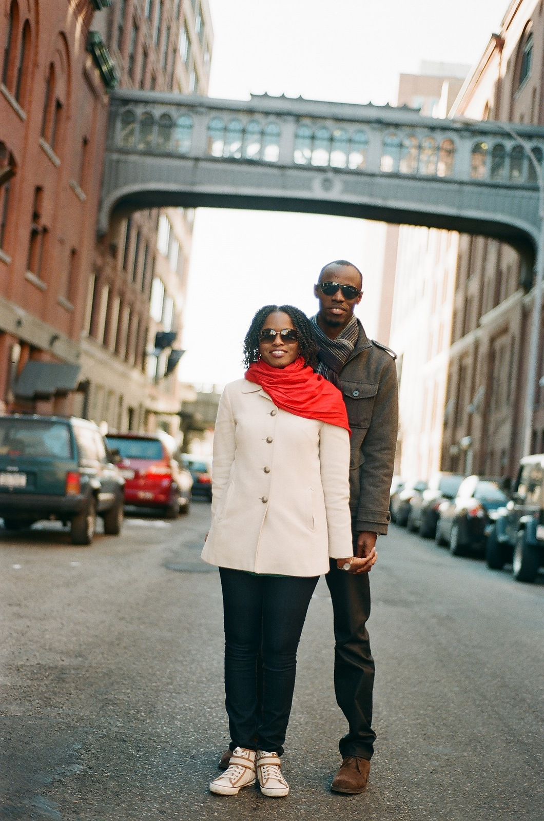 engaged couple standing below overpass in downtown nyc