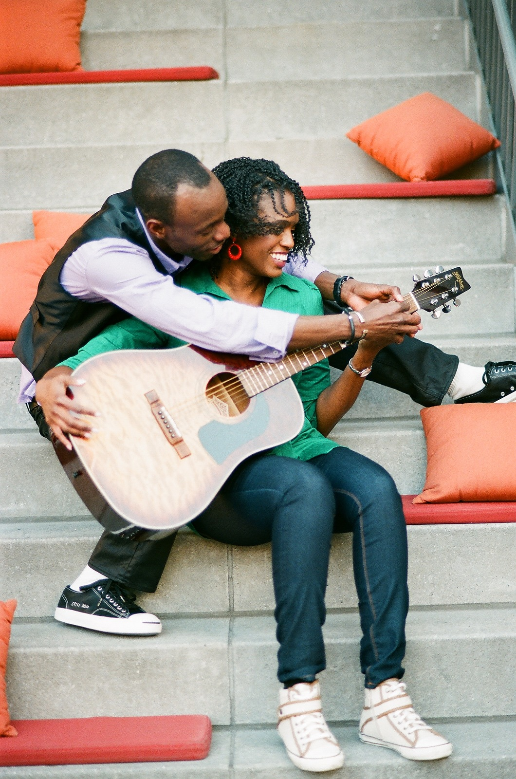 engaged couple sitting on steps with guitar
