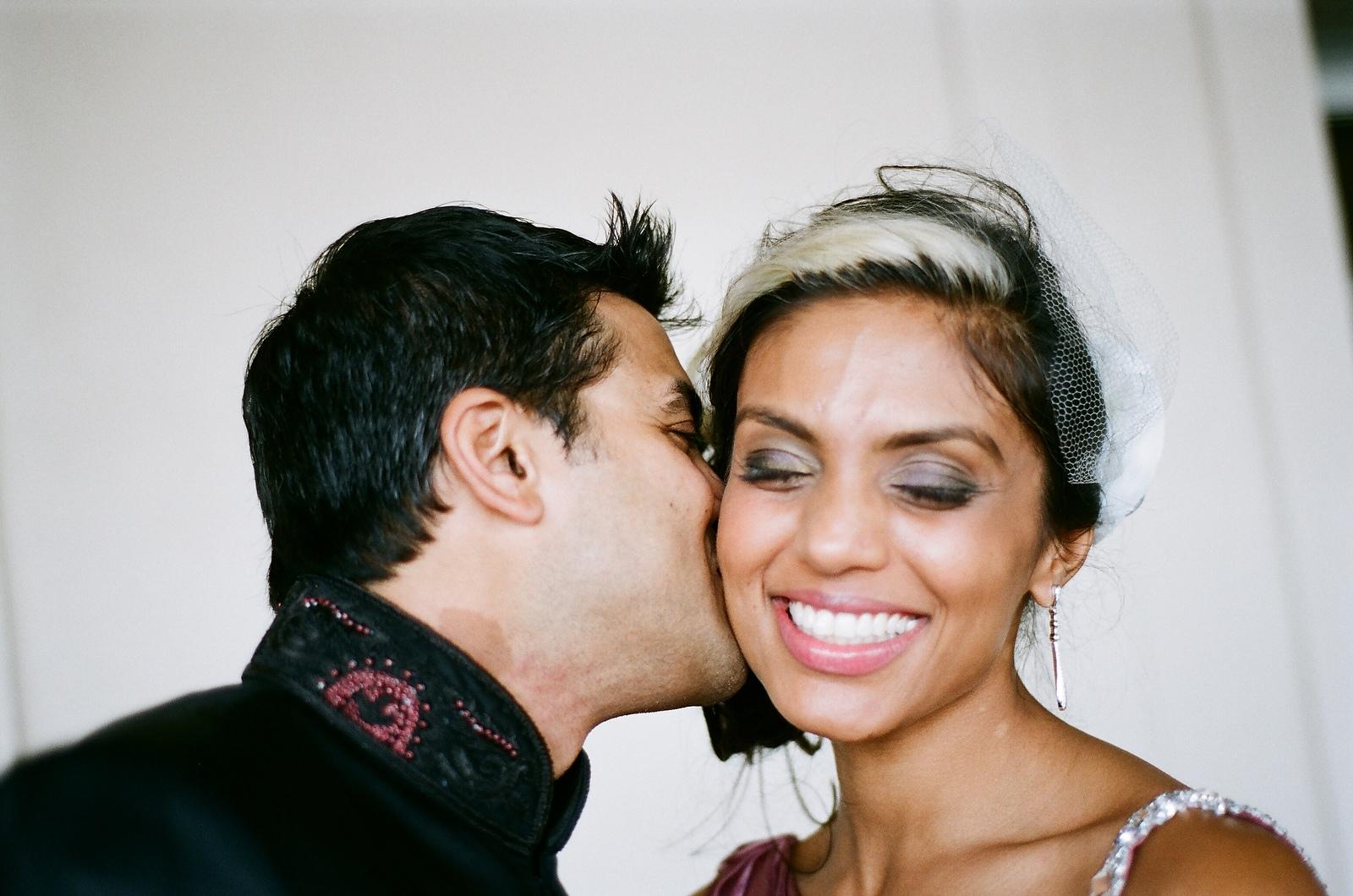 groom kissing laughing bride