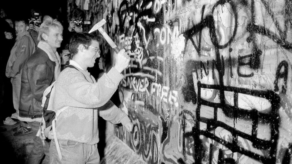 1989年11月9日,在西德宣布開放邊界後,一位男子用鐵錘敲擊靠近勃登堡門附近的柏林牆。