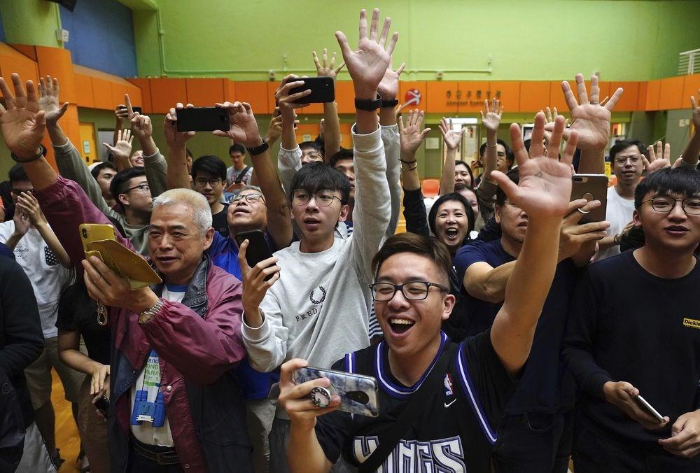 香港泛民主派在區議會選舉中大獲全勝,篤定將可以取得特首選舉委員會1200席中的117席。圖為泛民派候選人確定當選後,支持者歡呼慶祝。(美聯社)