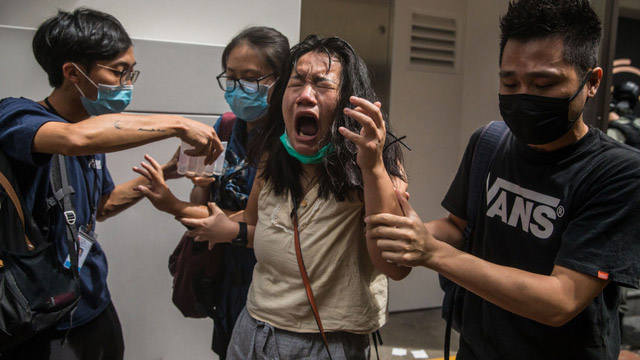 七月一日港警发射催泪弹和胡椒喷雾驱散民众,一名女子露出痛苦表情。(法新社)