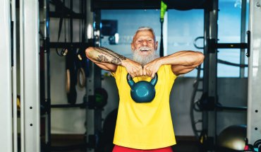 Hipster senior man training inside home gym