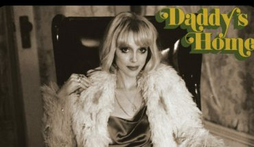 St. Vincent Daddy's Home album cover. Annie Clark is sitting on a chair in a silk dress and fur coat in a sepia tone photograph.