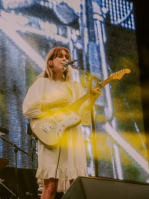 Singer songwriter Ellis is performing on stage. She is wearing a white dress and singing into a microphone. She is playing a green and white electric guitar.