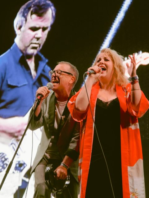 Torquil Campbell and Amy Millan of the band Stars singing together on stage. They are leaning against each other and singing passionately.