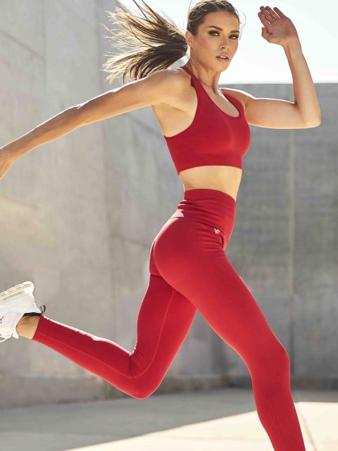 A woman is wearing V Shred fitness apparel while running. She is wearing a red sports bra and red yoga pants with white running shoes.