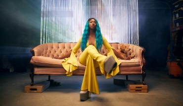 Domanique Grant press photo. Domanique is sitting on a vintage pink couch wearing a yellow jumpsuit