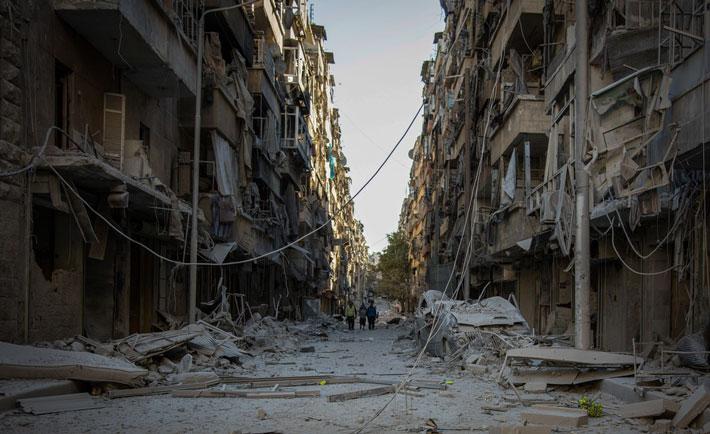 (Foto di KARAM ALMASRI) Persone che camminano lungo una strada nel quartiere Bustam Al Kasr dopo essere stato colpito da un attacco aereo nella metà di ottobre del 2016.