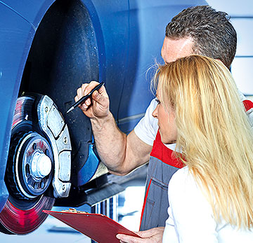 Werkstatt-Meister erläutert Kundin den Reparaturbedarf.