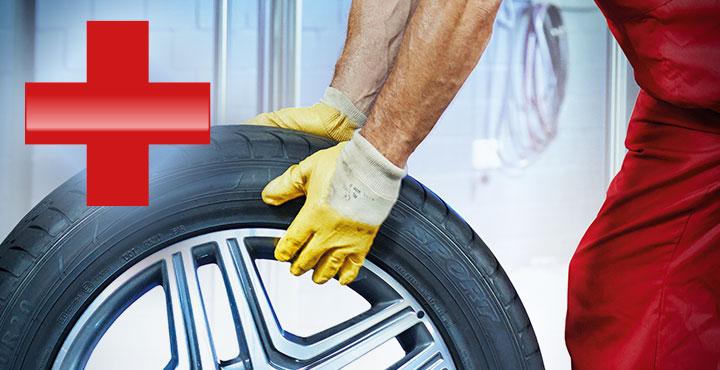 Mechaniker beim Radwechsel – rotes Pluszeichen