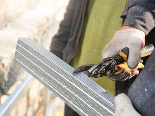 Builder cutting metal profile with metal scissors