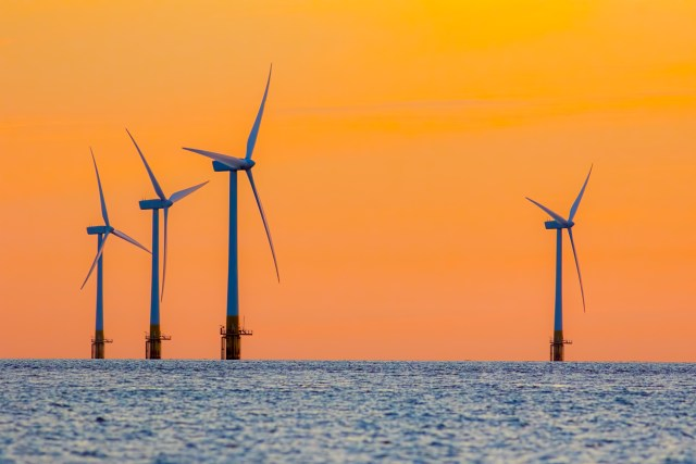 Offshore wind farm energy turbines at dawn. Surreal but natural sunrise at sea.