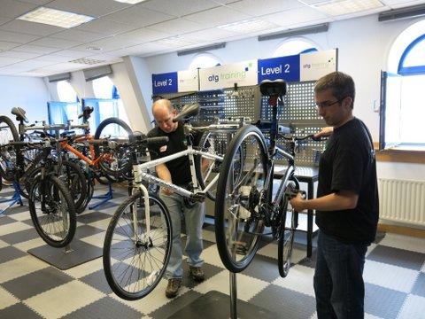 Two people fixing bikes