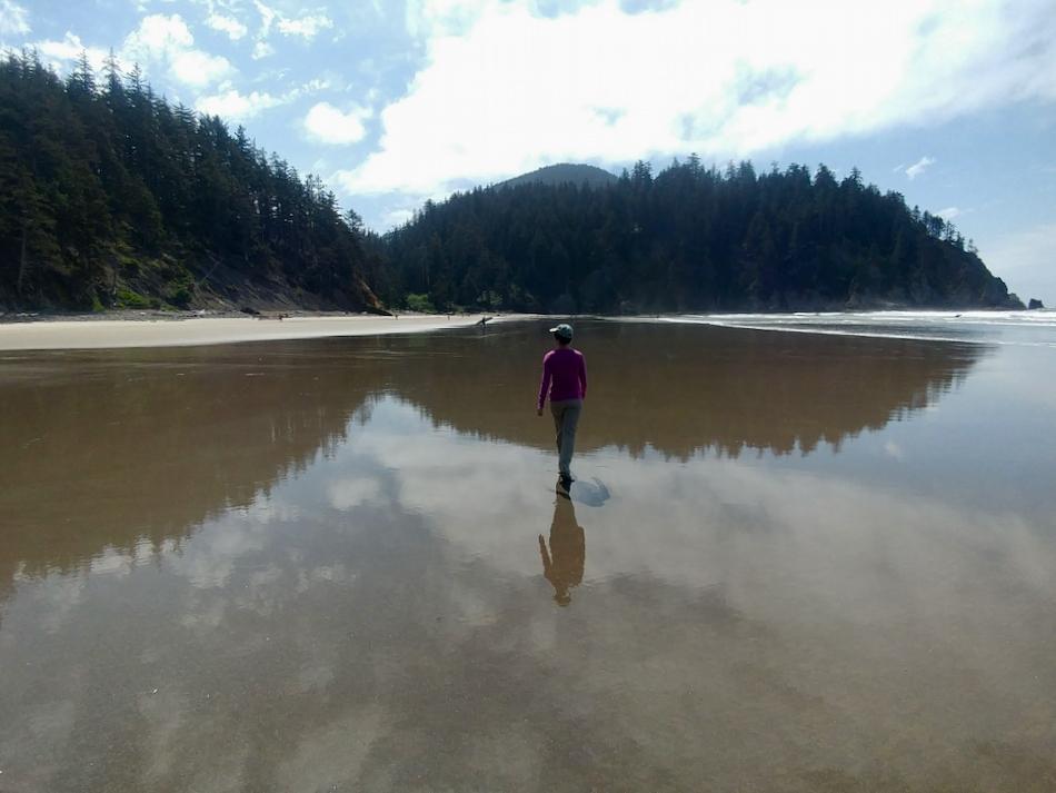 Person walking on flat sandy beach