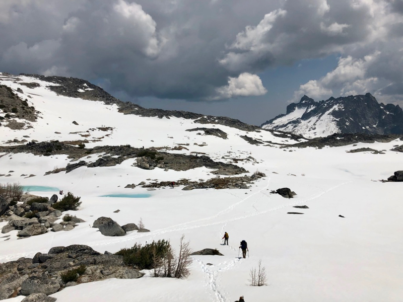Two hikers walking on snow in a rocky landscape