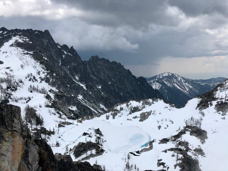 Snowy alpine lake below a dark rocky mountain peak.