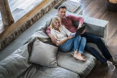 Couple sitting on couch, using laptop