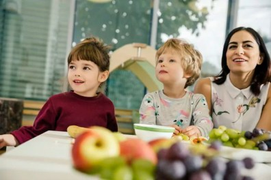 Children and teacher sitting at table with fruit in kindergarten