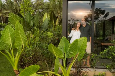 Garden view of smiling couple looking outside of their design house surrounded by lush tropical garden