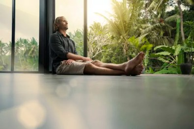 Handsome man sitting on floor and leaning on glass facade with stunning tropical garden in background
