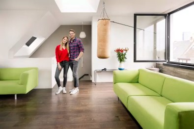 Portrait of smiling young couple standing in living room at home