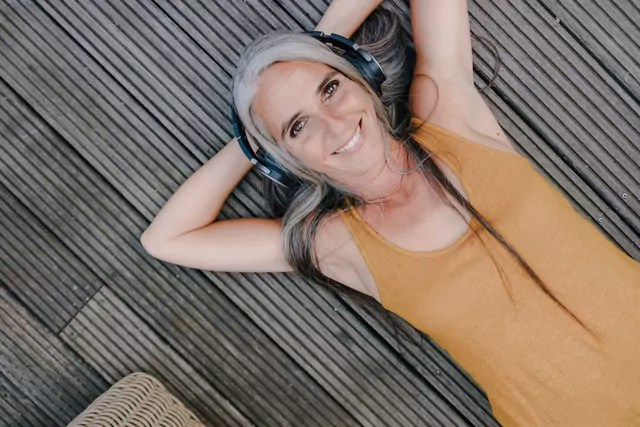 Portrait of happy woman lying on terrace listening music with headphones