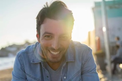 Portrait of laughing young man on the beach at sunset