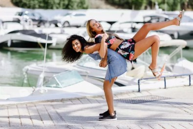 Two playful young women at waterfront promenade in summer