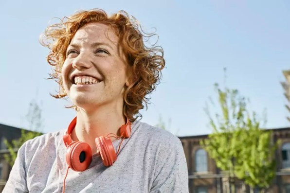 Portrait of happy young woman with headphones in urban surrounding