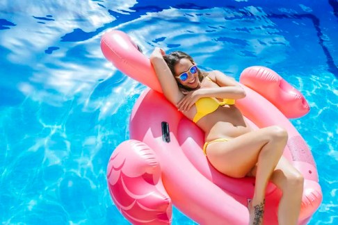 Carefree young woman on pink flamingo float in swimming pool