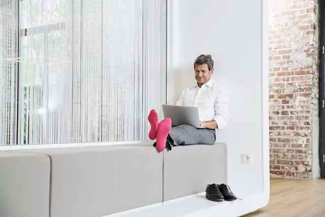 Businessman with pink socks using laptop in office