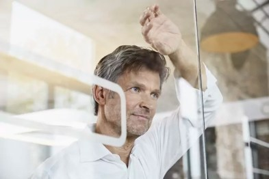 Portrait of mature businessman leaning against glass wall in office