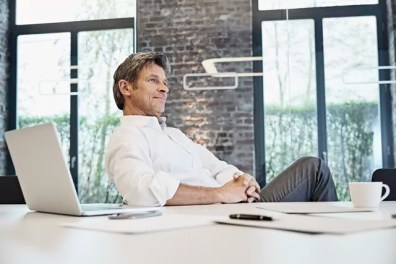 Mature businessman with laptop in modern office