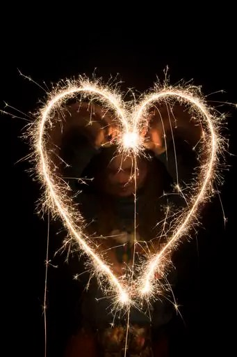 Teenage girl painting heart with sparkler at night