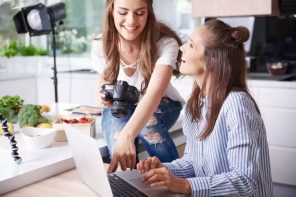 Happy bloggers using laptop in kitchen