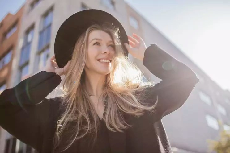 Portrait of happy woman with hat dressed in black