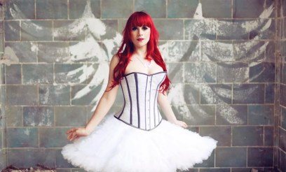 Portrait of woman with red hair and ballerina dress standing in front of wall with angle wings graffiti