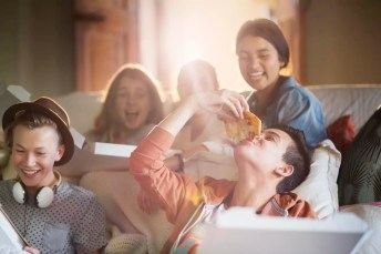 Group of teenagers eating pizza on sofa in living room