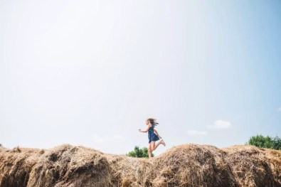 Carefree girl running on heap of hay against sky