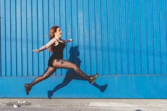 Woman in front of blue wall jumping in mid air