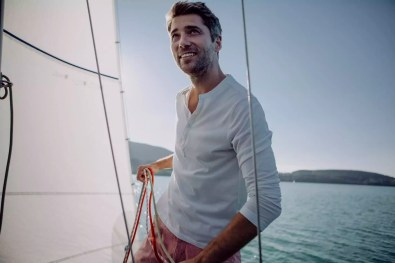 Smiling man standing on a sailing boat