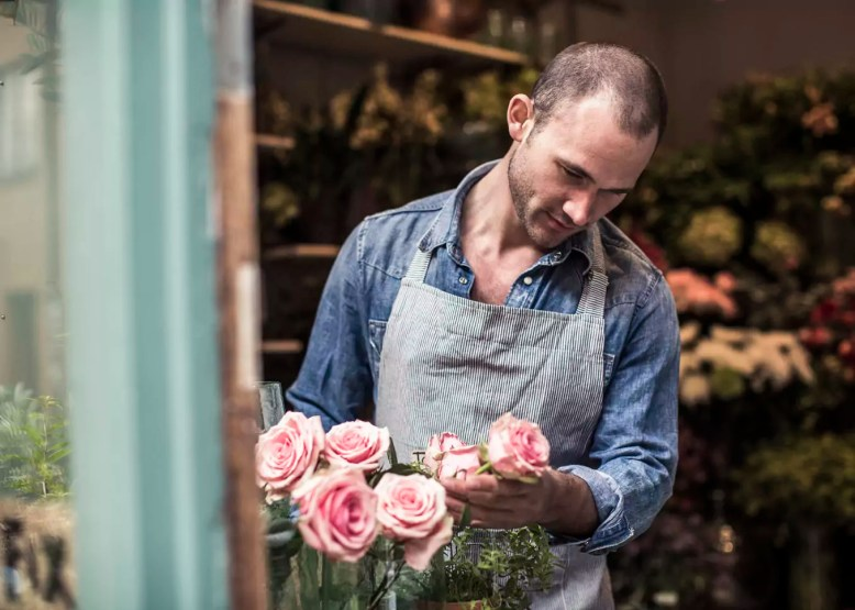 Mid adult male florist analyzing flowers at shop