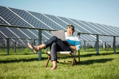 Mature man sitting in beach lounger, using laptop, solar plant