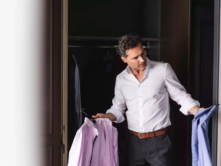 Businessman at home getting dressed choosing shirt from wardrobe