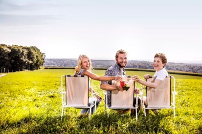 Happy friends sitting on camping chairs in rural landscape clinking bottles
