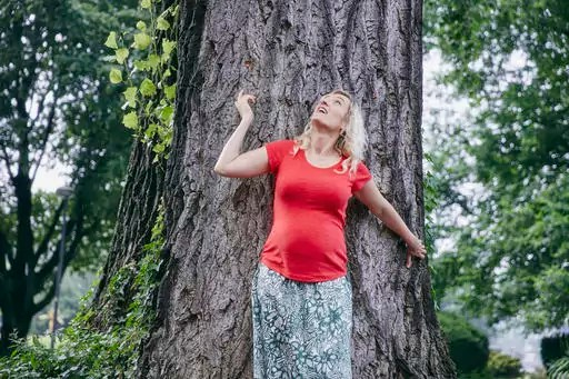 Smiling pregnant woman standing at a tree in park looking up