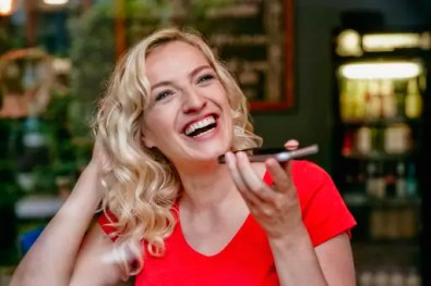 Portrait of laughing blond woman using smartphone in a cafe